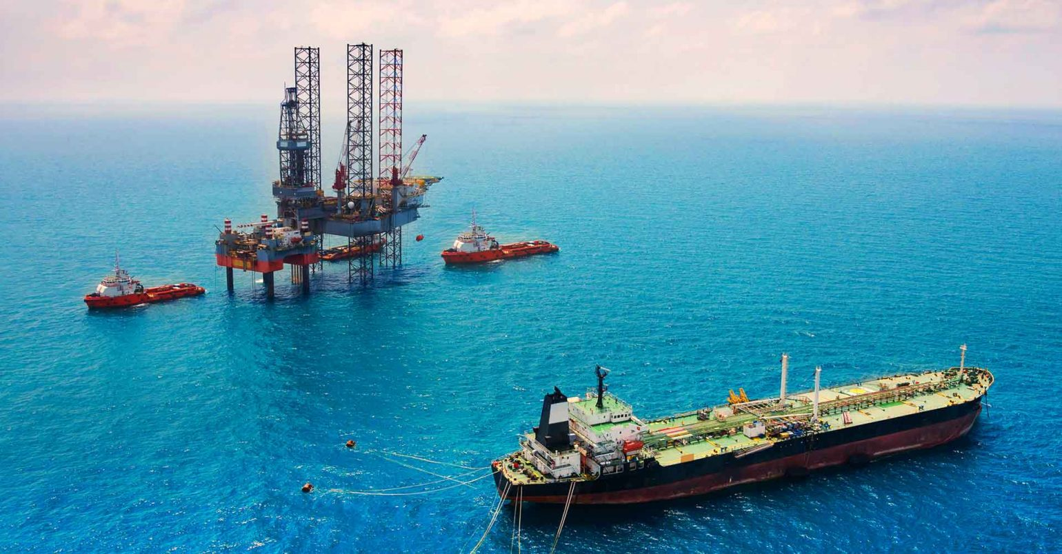 Photo of an oil tanker and oil rig at sea.