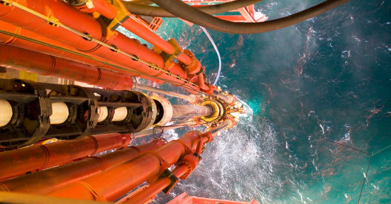 Closeup photo from oil rig with pipes extending down into the sea.
